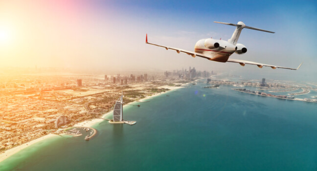 Private,Jet,Plane,Flying,Above,Dubai,City,In,Beautiful,Sunset