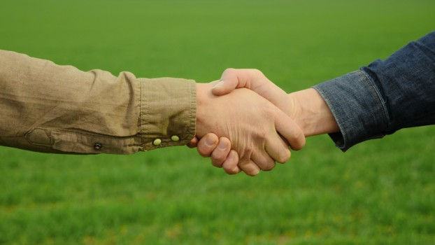 Friendly,Handshake,,Two,Farmers,Shaking,Hands,Against,The,Background,Of