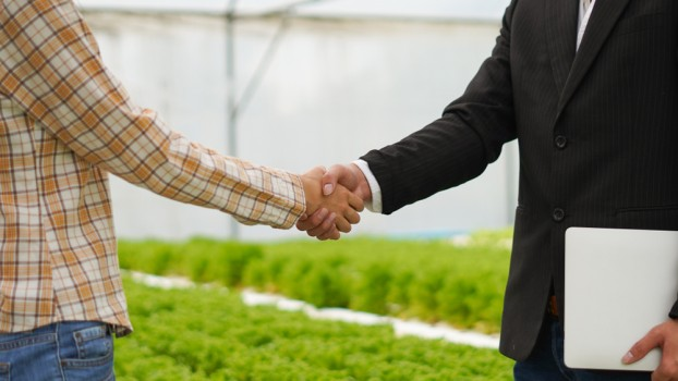 Agribusiness,Concept,,Farmer,And,Businessman,Shaking,Hand,With,Hydroponic,Farm