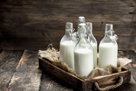 Bottles,With,Fresh,Milk,In,A,Box.,On,A,Wooden