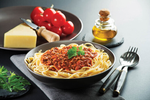 Delicious,Spaghetti,With,Bolognese,Sauce,Served,On,A,Black,Plate