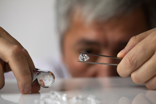 Man,Jeweller,Looking,At,Pear,Shape,Diamond.,Holding,In,Hand.