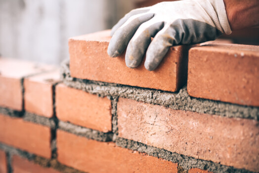 Close,Up,Of,Industrial,Bricklayer,Installing,Bricks,On,Construction,Site