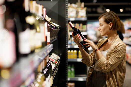 Girl,In,White,Jersey,And,Jacket,Chooses,Wine,In,Supermarket.
