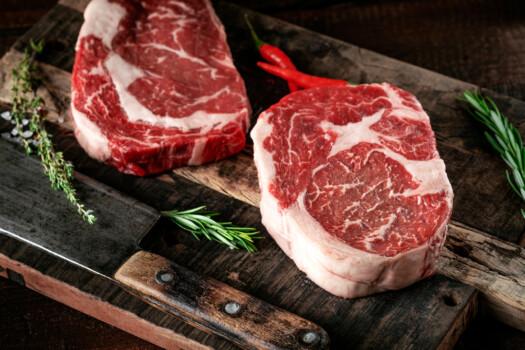 Raw,Rib,Eye,Steak,Of,Beef,On,A,Wooden,Board